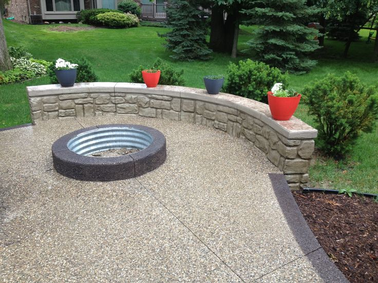 Exposed Aggregate With Pre Fab Fire Pit Ring And Rock Face Garden Wall
