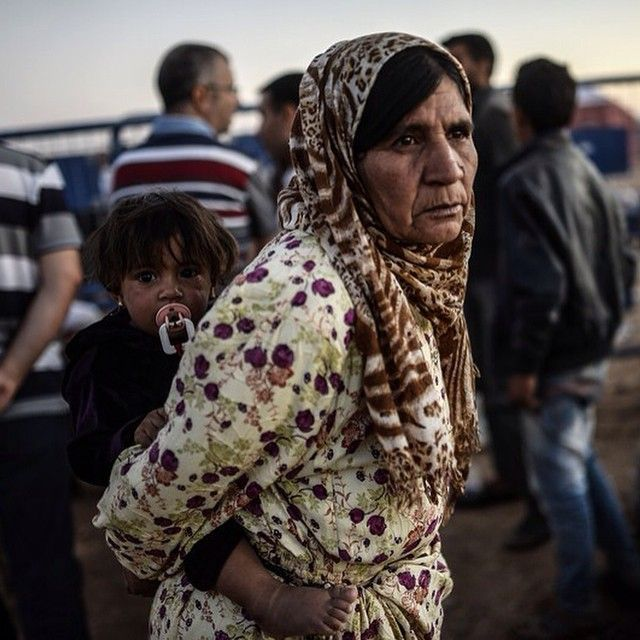 A Syrian Kurdish #refugee holds a baby as she waits after crossing the border into Turkey. Tens of thousands of Syrian #Kurds made the same journey on September 20, fleeing an onslaught by the jihadist Islamic State group.