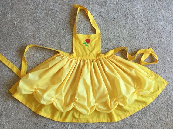 Pictured is 21 apron on size 8 model. Belle princess apron with crown motif embroidered on bib. Great for little girls dress up or princess party! Toddler size fits 18mos. - 2 years and has a 5 bib and 14 skirt. Size 3-6 has 7 bib and 17 skirt. Size 7-10 has 7 bib and 21 skirt. Adult size has 10 bib and 24skirt. Please allow 2-3 weeks for completion of apron. 15 aprons available for costum order: Rapunzel, Snow White, Belle, Cinderella, Sleeping Beauty, Ariel, Tiana, Bride, Minnie, Anna…