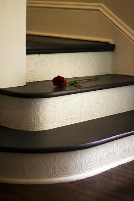 Add paintable and textured wallpaper on the stair risers - great DIY project, and affordable - under 30!