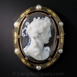 The best of the best! A classical alabaster beauty and her flowing tresses are masterfully captured in high relief in this exceptionally lovely Victorian hardstone cameo brooch of surpassing quality. She is elegantly presented in a frame of rich 18K rose gold embellished with striking black enamel, six lustrous natural pearls and as many tiny glinting rose-cut diamonds set on the prongs. A superb and stunning work of wearable art measuring 2 by 1 5/8 inches.
