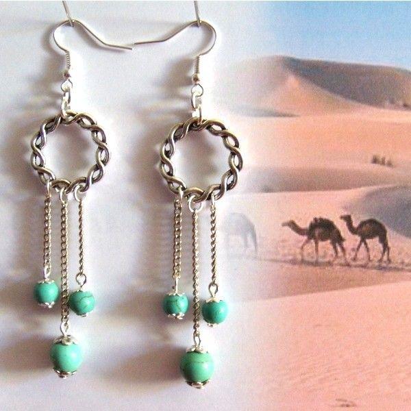 3 perles qui se balancent gracieusement  au bout de 3 chaînettes fines suspendues  à 1 anneau tressé.  Perles d'imitation  Apprêts couleur argent mat  Longueur: 7 cms (à partir de l'attache)