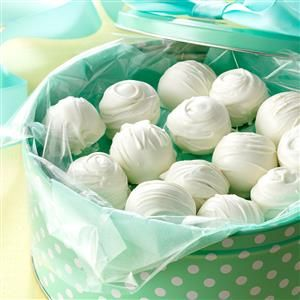 Peanut Butter Snowballs Recipe -These creamy treats are a nice change from the typical milk chocolate and peanut butter combination. This recipe is also an easy one for children to help with. I prepared the snowballs for a bake sale at my granddaughter's school and put them in gift boxes I share with neighbors at Christmas. —Wanda Regula, Birmingham, Michigan