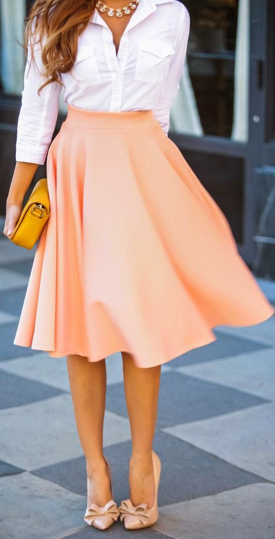 white blouse shirt with pink stylish medium pleated skirt and amber leather clutch and pink stylish high heels pumps and cute necklace.