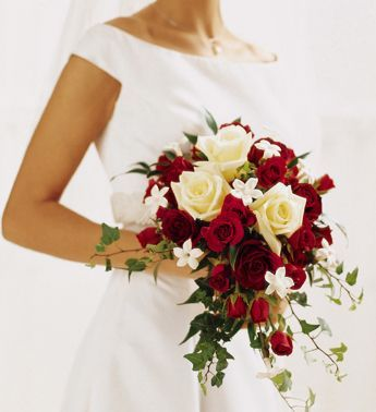 small cascading bouquet with red garden roses, seeded eucalyptus, berries, peonies, anemones and maybe pincushions.