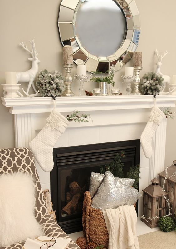 BERRIES AROUND WHITE CANDLES SITTING ON HOLDERS....DO FOR CHRISTMAS OR WINTER!!!  neutral mantel decor with silver candle holders and vases, a deer and flocked fir balls