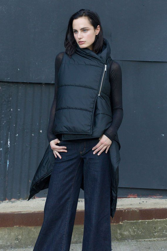 a2a6a6aded6b Play up your cool weather look with this black puffer vest with asymmetrical  hem. The front features a chunky high collar and a side zipper closure.