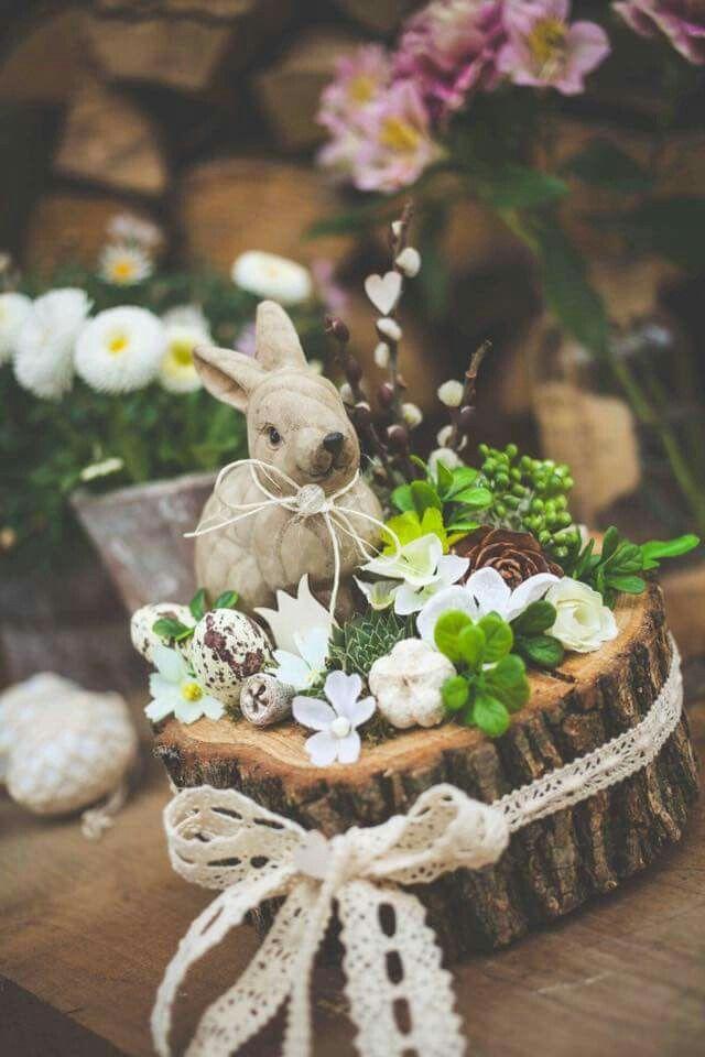 Hase auf Baumscheibe mit Blumen. Osterdekoration. – Ostern