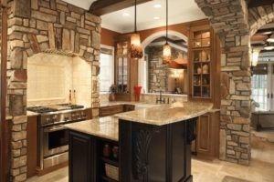 Dies ist eine gehobene rustikale thematische Küche mit Bögen. Ein Bogen dient der Küchenbar während, behaart und drywalled Ziegel diejenigen die das enthalten einer Einbau Edelstahl Stahl Wut mit Dunstabzugshaube und die andere dient als Eingang in die Küche. Es hat auch Kücheninsel mit Granit-Arbeitsplatten. Die Pendelleuchten sind auch Schönheit hinzufügen. Quelle: homeepiphany.com
