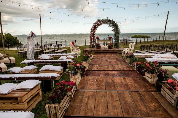 Cerimònia de casamento com vista para a praia, deck em madeira, arco de flores com bancos e pallets para os convidados. Foto: Rafael Bigarelli