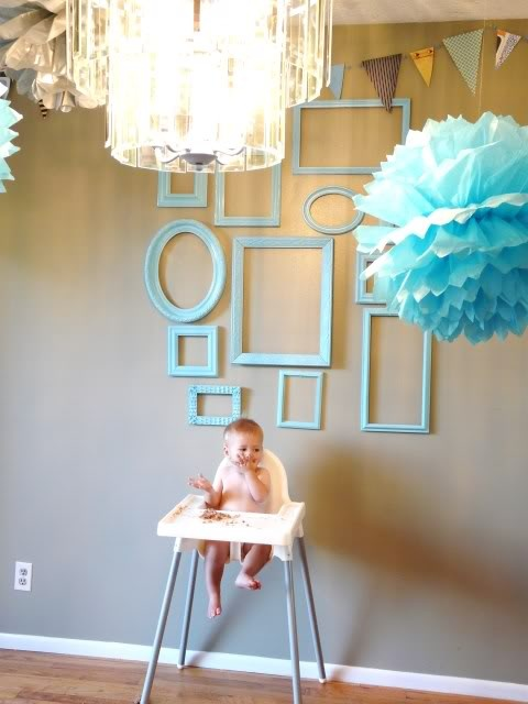 empty frames on the wall.  and a cute baby.
