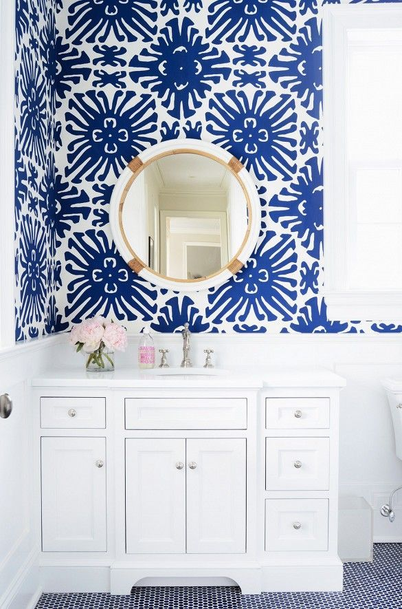 Blue and white wallpaper with round mirror in bright bathroom