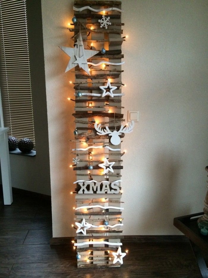 Wandrek gemaakt van planken van een pallet en losse takken uit het bos, versierd met lampjes en kerst decoraties.