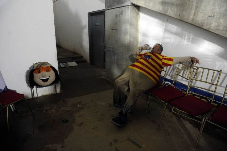 """The man that works as the mascot """"Margarito"""" for the 2014 Caribbean baseball series rests at the backstage during a game between Dominican Republic's Tigres de Licey and Venezuela's Navegantes del Magallanes in Porlamar city, Margarita Island, Nueva Esparta state, Venezuela, Feb. 4, 2014.  LEO RAMIREZ—AFP/Getty Images"""
