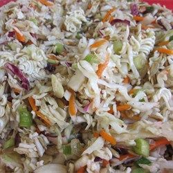 Bagged coleslaw mix is combined with crunchy dry ramen noodles, sunflower seeds, almonds, green onions, and a simple sweet vinaigrette for a tasty Asian-inspired coleslaw.