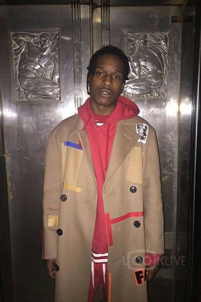 ASAP Rocky wearing  Raf Simons Double Breasted Camel Coat, Guess x A$AP Rocky Striped T-Shirt, Gosha Rubchinskiy Printed Track Trousers