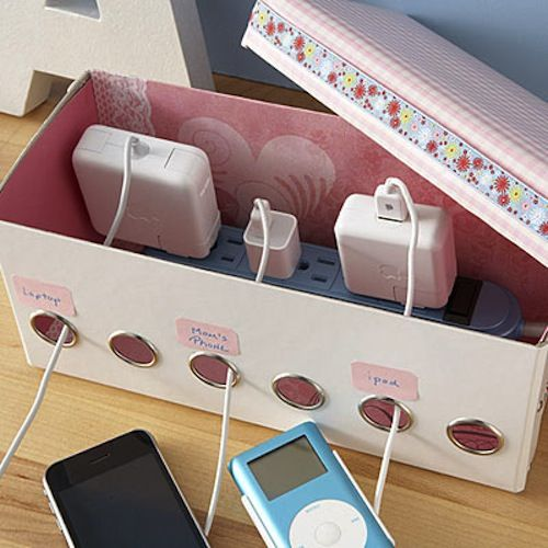 HOMEMADE CHARGING STATION. Keep those cords and power strips hidden with your very own charging station made out of a ribbon dispenser box from The Container Store. Use a utility knife to cut a hole for your power strip cord to pass through, label the holes, and decorate the box!