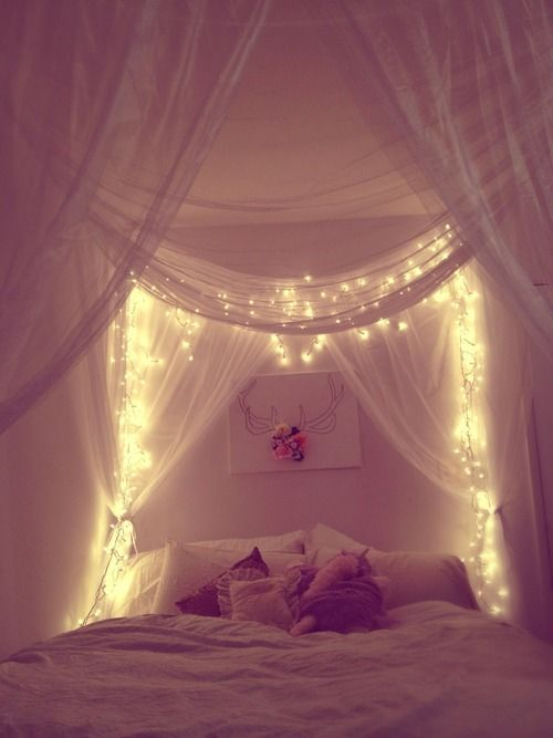 I once had a bed with a lacey canopy like this -- but it didn't have fairy lights to make it magical.