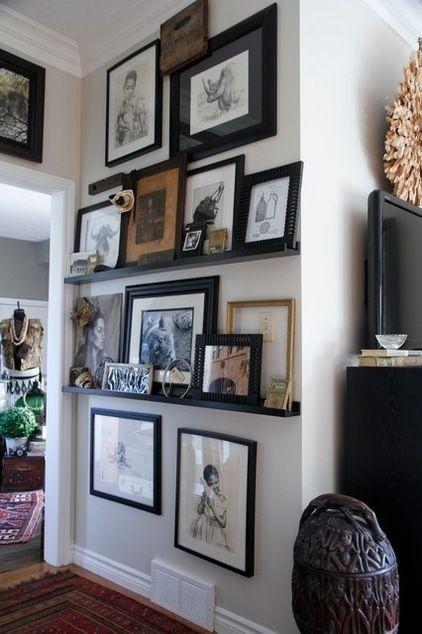 Gallery wall mesclando quadros apoiados com quadros pendurados preenchendo a parede toda