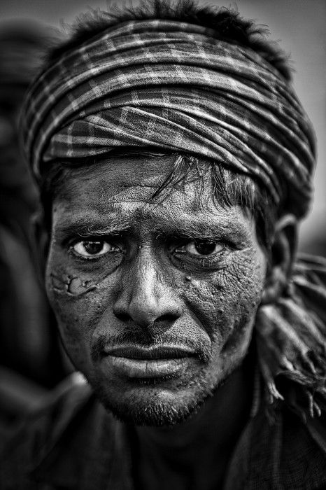 Bokahapadi, Jharkhand, India. Portrait of a miner in a coal mine. The world is black in Jharkhand, northeastern India. The entire area around the cities of Dhanbad, Jharia and Catras is full of coking coal, a treasure for the Indian economy (two thirds of all electricity in India is generated from this coal). Black dust and gasses shoot up from the ground: methane, carbon monoxide are in the air and many of the people who live and work in the region suffer for letal respiratory problems…