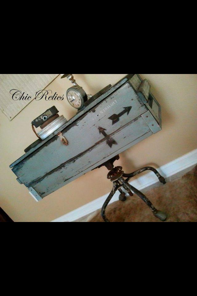 Wooden ammo box on vintage metal swivel chair/stool legs.