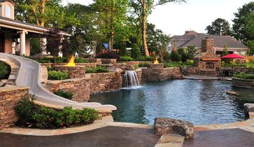 PARADISE REGAINED - This backyard has a pool that looks like a sparkling lagoon, water slide and waterfall included! The decorative stone wall continues along into the stone oven, pulling the entire area together.  Photo by J. Brownlee Design