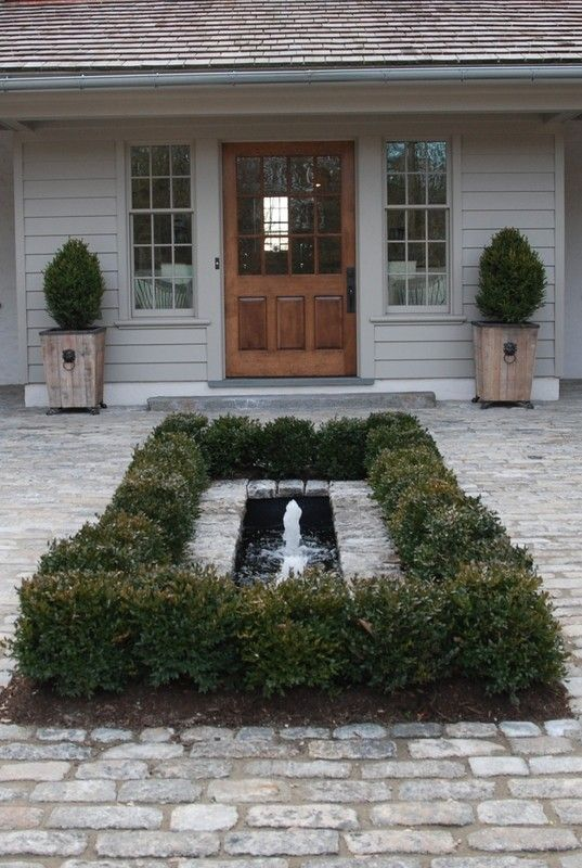 If you've got a large open driveway in front of your house, here's a good idea to break up the space and add beauty and visual interest. The fountain and narrow pool in the middle of the brick drive is surrounded with a low hedge, and the potted shrubs flanking the door complete the look. For beautiful hardscapes in Minneapolis MN, contact http://aldmn.com