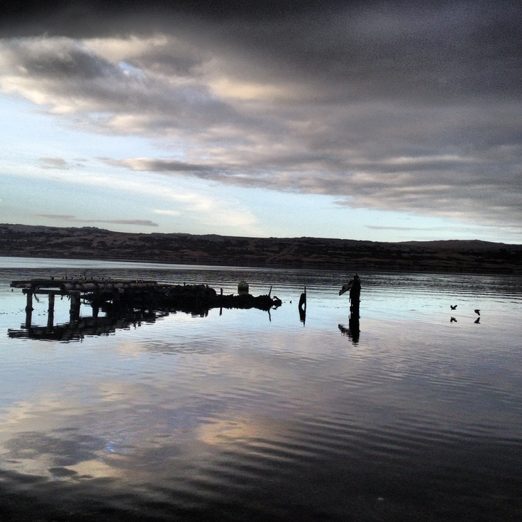 Taken by me on a calm evening, this is The Old Jetty in Stanley (Falkland Islands - where I currently live). You can't miss it. If you travel along the front road/Ross Road, you'll go by it.