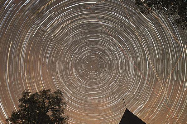 """Über dem Kirchturm von Wollseifen zielt der Fotograf auf den """"ruhenden Pol"""" des Nachthimmels, den Polarstern. Um ihn scheinen sich die anderen Sterne zu drehen. Bei der langen Belichtungszeit zeichnen sie Kreissegmente. <small>Bild: Harald Bardenhagen</small>"""