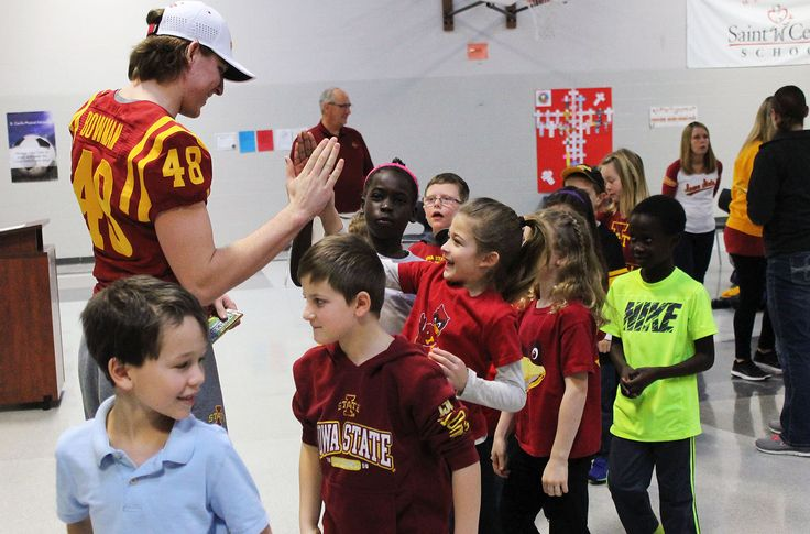 Iowa State football player Jason Bowman gives high fives to students during an assembly at St. Cecilia for Catholic Schools Week. Photo by Sarina Rhinehart/Ames Tribune  http://amestrib.com/news/coach-prohm-pays-surprise-visit-st-cecilia-school