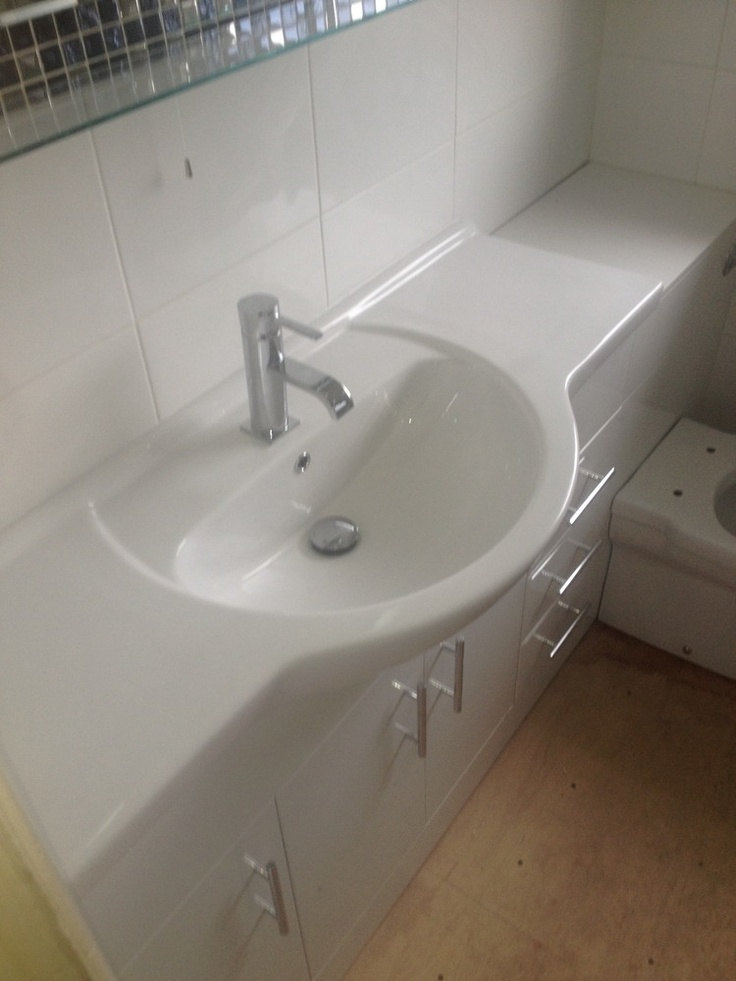 Bathroom sink fitted into fixed unit with lots of storage - classic white colours