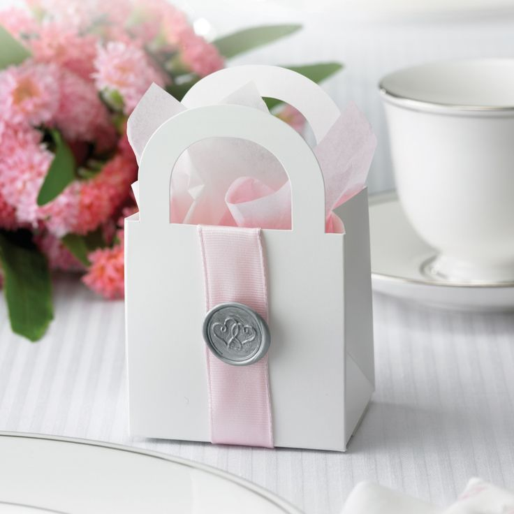 These are cute - you can put anything in them from a candle to a picture to a box of matches. AND we can probably buy the little bags anywhere and put the ribbon and things on them ourselves if we're pushing the budget. I'm sure there are lots of ideas like this.