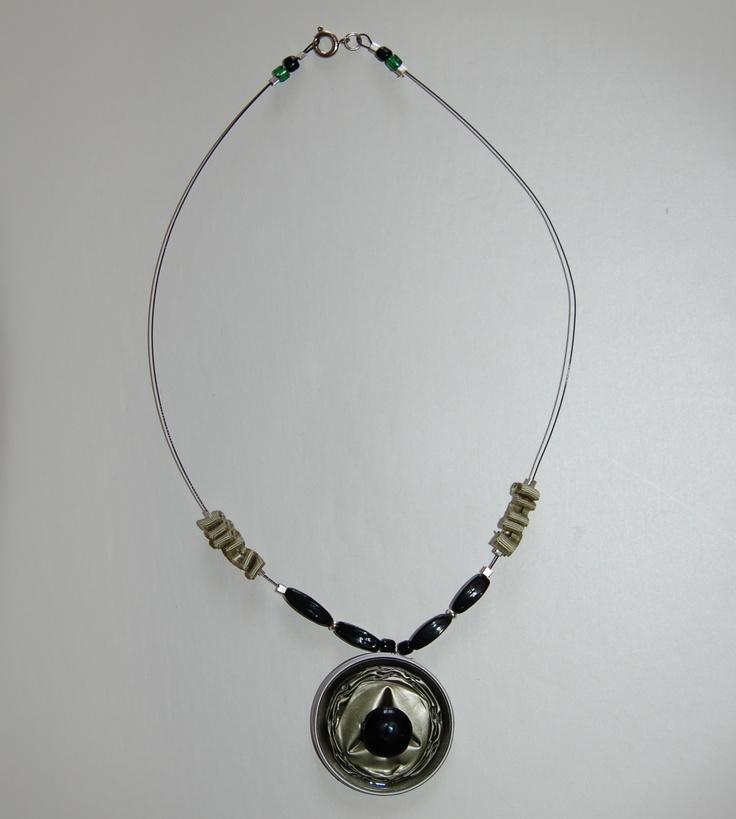 Collana in filo di acciaio nero, nastro grosgrain verde, perline nere, ciondolo cialda Nescafé con perlina nera. Chiusura a molla.