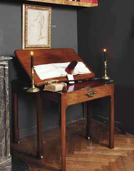 A GEORGE II MAHOGANY ARCHITECT'S TABLE CIRCA 1760 With a rachetted top, a pair of circular candleslides and slides to the sides, above a fitted pull-out front drawer with hinged red suede-lined writing surface, enclosing compartments, on square legs terminating in brass castors
