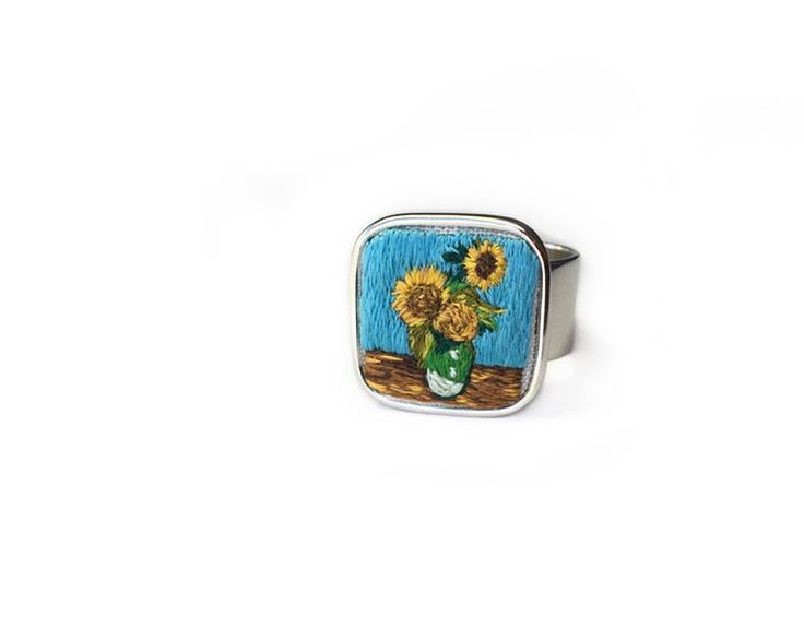 """Vincent van Gogh has always been one of my favorite artists. I was inspired to replicate the brushstrokes of his art with tiny stitches in this miniature embroidery ring. This ring is a miniature recreation of his Sunflowers in Green Vase. The ring is hand embroidered in silk and one of a kind. Many hours go into each piece and they are inspired from my love of art history. I hope you find something in my shop that you love. The ring measures 18mm and has a 3/8"""" wide, ..."""