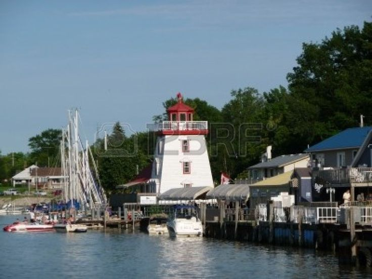 Lighthouse in the harbor in Grand Bend Ontario Canada, with sailboats and boardwalk in the foreground, blue sky and trees in the background