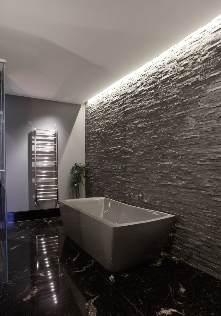 stone wall raked by recessed lighting  KNIGHTSBRIDGE RESİDENCE LONDON...