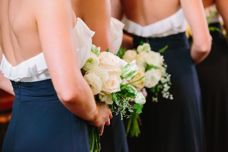bridesmaids in navy gowns carry bouquets of white roses, champagne roses, green parrot tulips, white ranunculus and fresh greenery.
