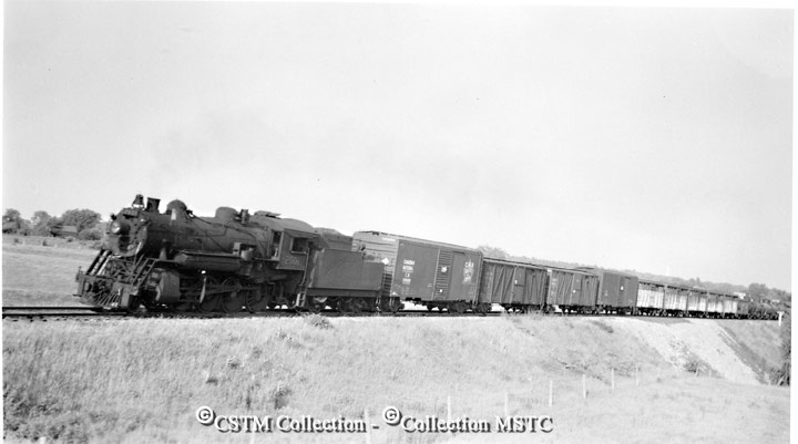 """Date: 1956-05-00  Caption: """"CN locomotive #2601 on a freight train leaving Arnprior just prior to diesels, which were introduced on May 15th, 1956 when steam was displaced forever on freight trains."""""""