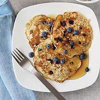 """""""If you cook with flavor,"""" says Iron Chef Cat Cora, """"then the nutrition will naturally follow."""" That's why Cora uses whole milk, which health-conscious runners typically avoid, in her walnut and blueberry bran pancakes. """"Fat is flavor,"""" she says. """"You just need a little bit to get the taste and to feel satisfied. It's worth running the extra miles.""""1 1/2 cups whole milk1 cup instant oats3/4 cup sifted all-purpose flour (or a blend of white and whole-wheat flours)3/4 cup blueberries1/2 cup…"""
