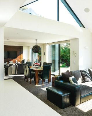 Vaulted ceilings and high windows give a sense of space and light in the living room; at the far end is a television ...