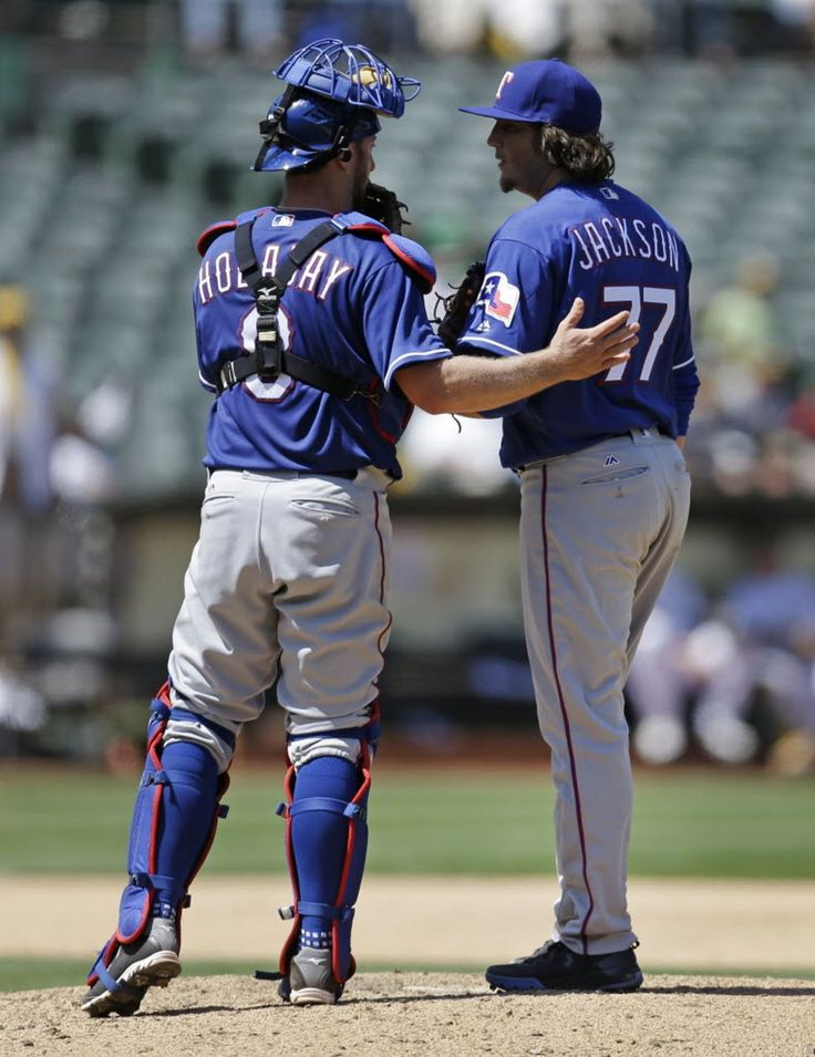 Texas Rangers catcher Bryan Holaday, left, speaks with pitcher Luke Jackson during the eighth inning of a baseball game against the Oakland Athletics on Wednesday, May 18, 2016, in Oakland, Calif. The A's won 8-1. (AP Photo/Ben Margot)