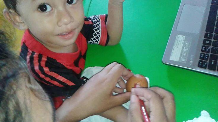 I bambini colorano le uova, con le loro mamme, a scuola