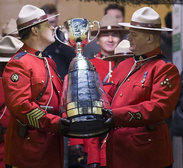 One of the RCMP officers kisses the cup as he prepares to walk it onto the field at the beginning of the 103rd Grey Cup between the Edmonton Eskimos and the Ottawa Redblacks on Nov. 29, 2015 in Winnipeg. Photo by Greg Southam / Edmonton Journal