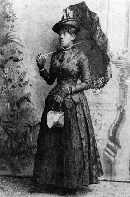 Lottie Campbell, c.1888.    I would date this to the late 1880s because of the tail bodice, a style dating back to around 1883 but which remained popular until the 1890s. If you look at the back of the bodice, you can see it has tails that extend all the way down to the hem of the skirt.    Fingerless gloves.    Her hat looks like it has skyscrapers on it, which is probably not right but awesome.
