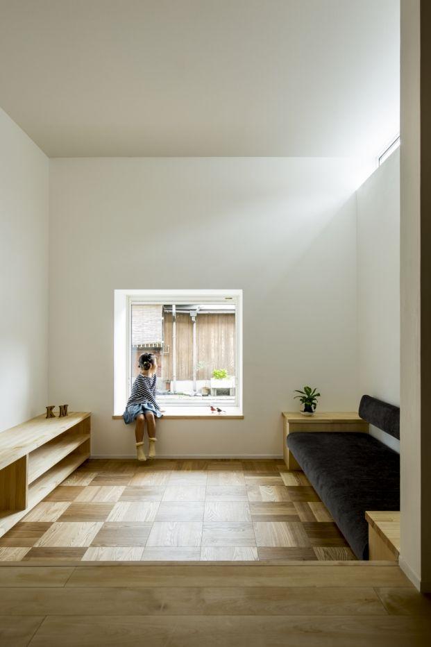 Parqué de madera en cuadrados, casa japonesa. Niña japonesa delante de la ventana.