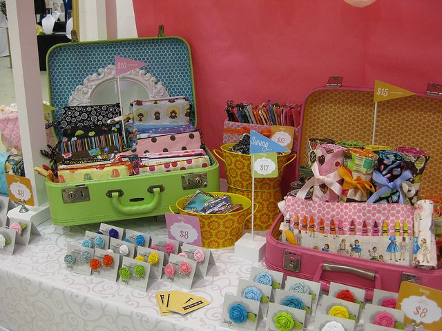 Love the suitcases, flag signs and Sweet colors in this craft show display.