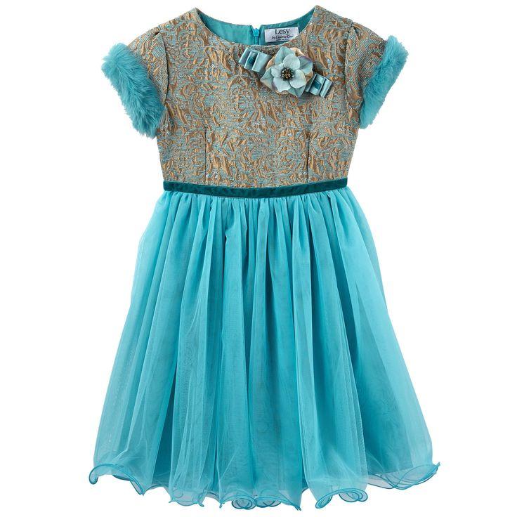 Великолепное нарядное платье из золотого брокарда и бархата синего цвета, украшенного блестящим люрексом, в верхней части и на рукавах. Пышная и сильно расклешенная юбка из воздушной сетки. Синтетическая подкладка. Круглый вырез горловины и короткие рукава, отороченные мехом кролика. Потайная молния на спинке. Пояс, украшенный бархатной лентой, завязываемый на спинке. Съемная брошь в виде цветка