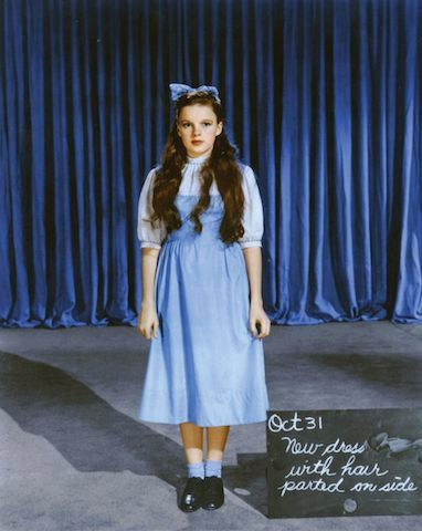 Test Photos There were several different pinafores costume designers explored using in The Wizard of Oz before settling on the famous gingham dress worn by Judy Garland. They also tried out various wigs (including a blonde one), makeup styles (one very baby-doll-esque), and shoes (one pair Arabian in style). Judy's stand-in also had her own dress -click the link, it's neat