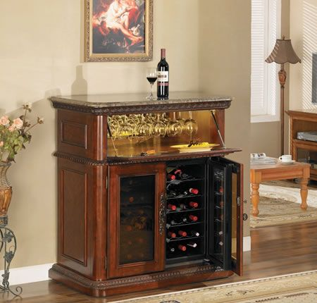 The Rutherford features an interior lighted hidden storage area with stemware racks, concealed by an expertly crafted drop down lid that doubles as a work surface.  Double doors lock to secure 2 coolers with independent temperature control with room for 36 wine bottles.  A prominent carved molded base and polished marble top with hand carved border round out this sumptuous wine cabinet.